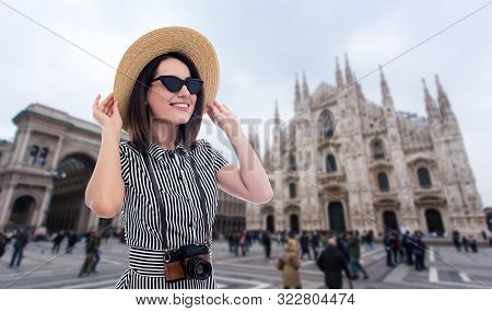 Portrait Of Young Beautiful Woman Tourist In Straw Hat With Camera Over Duomo Cathedral In Milan, It