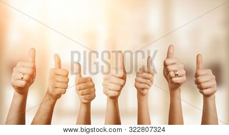 Close Up Of Group Of Hands Showing Thumbs Up Over Defocused Background With Copy Space