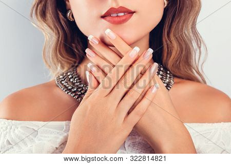 Nail Art And Design. Beautiful Woman Wearing Make-up And Jewellery And Showing Her French Manicure