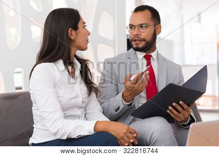 Mentor Explaining Document Specifics To Intern. Business Man And Woman Sitting On Office Couch With