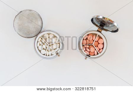 Top View Of Medical Tablets In An Opened Medication Box On White Background. Medication Concept.