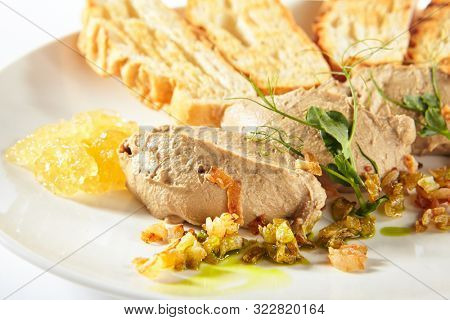 Chicken liver pate with crunchy baguette and fruit jelly sauce isolated on white background. Delicious duck or goose liver spread or foie with croutons on elegant restaurant plate poster