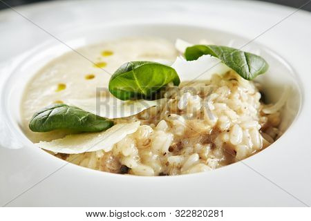 Beautiful Serving White Restaurant Plate of Risotto with Cep Mushroom Stew, Parmesan Cheese and Greens. Exquisite Delicacy Italian Boletus Paella on Dark Stone and Leaves Background