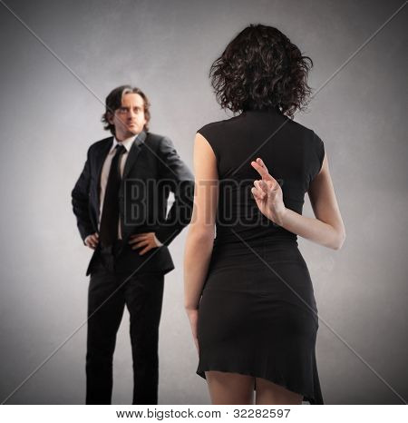 Insincere woman crossing her fingers behind her back with husband in front of her