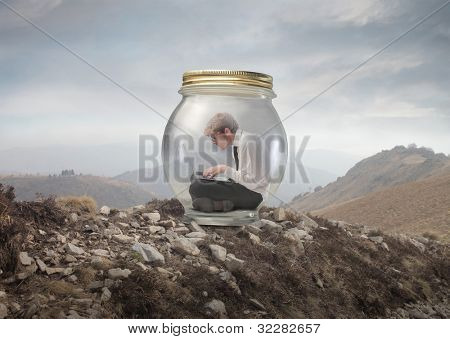 Young businessman trapped in a glass jar and using a laptop on a mountain peak