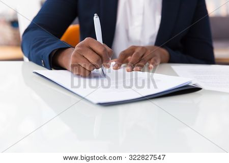 Businesswoman Signing Contract. African American Business Woman Sitting At Table In Office, Holding