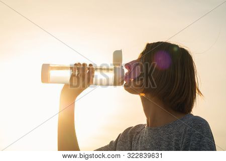 Young Woman Drinks Water From A Bottle On A Sunset Sky Background. Portrait Of A Female With A Reusa