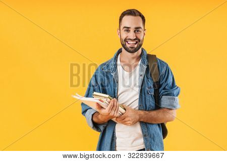 Image of content student guy in denim clothes smiling while holding exercise books isolated over yellow background
