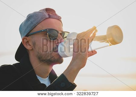 Young Man Drinks Water From A Reusable Bottle On A Hot Sunny Day. Portrait Of A Man With Water Bottl