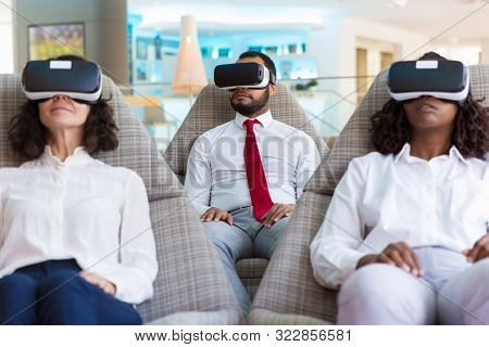 Group Of Colleagues In Vr Headsets Watching Virtual Presentation Together. Business Man And Women We