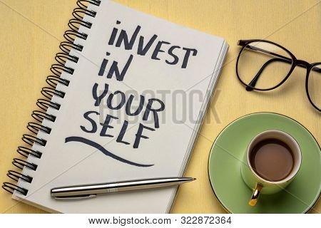Invest in yourself motivational advice or reminder - handwriting in a spiral notebook with coffee, personal development ans healthy lifestyle concept