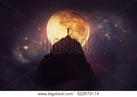 Self Overcome Concept As A Person Raising Hands Up On The Top Of A Mountain Over Full Moon Night Bac