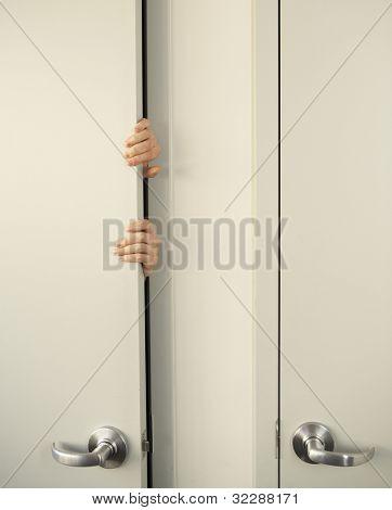 Businessperson clutching door-jamb