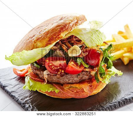 Fresh Beef Burger with Bacon, Fried Onions, Tomato Sauce, Pickled Cucumbers, Green Lettuce, Cheese and French Fries Garnish. Hamburger or Beefburger on Natural Black Stone Plate Isolated on White
