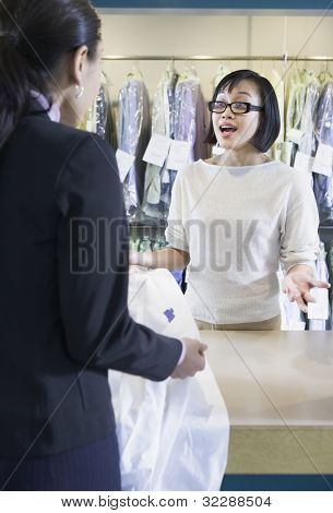 Asian drycleaner talking to customer