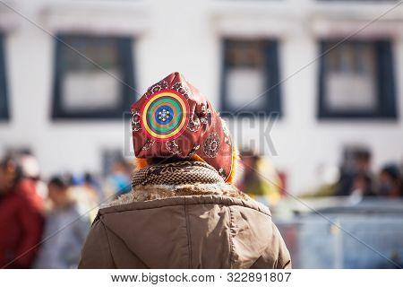 Lhasa, Tibet - January 28, 2019: A Pilgrim Wearing A Traditional Tibetan Hat Walks The Kora - A Type