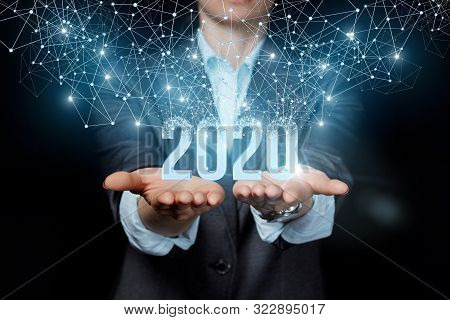 The New Concept 2020 In The Business. Businesswoman Showing 2020 On A Black Background.