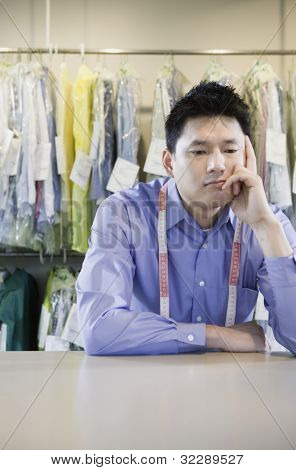 Bored Asian dry cleaner