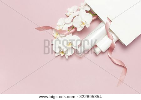 Flat Lay White Cosmetic Bottle Containers Gift Bag White Phalaenopsis Orchid Flowers On Pink Backgro