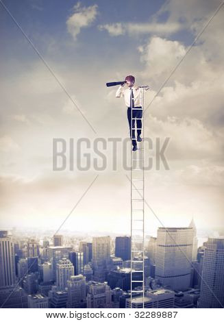 Young businessman on a ladder over a big city using binoculars