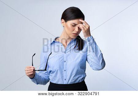 Ocular Hypertension. Tired Business Girl Massaging Nosebridge Having Eyes Fatigue Or Migraine On Whi