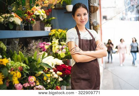 Young Female Business Owner Standing At Her Flower Shop. Young Entrepreneur Leaning With Her Arms Cr