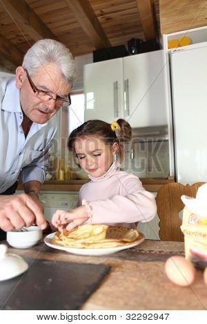 Elderly man preparing breakfast for granddaughter