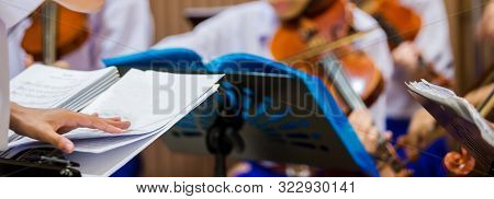 Selective Focus To Hands Of Conductor With Music Notation. Hands Of  Conductor With Blurry Asian Boy