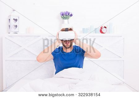 Virtual Reality Is Truly Here. Caucasian Man Wearing Virtual Reality Headset In Bedroom. Handsome Gu