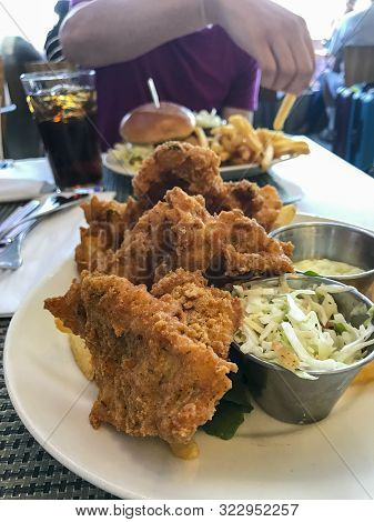 Traditional Southern Fried Chicken With French Fries On A Plate At A Restaurant