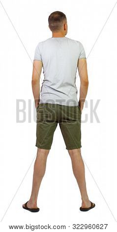Back view of young manin shorts looking. Rear view people collection. backside view of person. Isolated over white. A guy in shorts and slippers stands with his hands in his pockets and looks up.