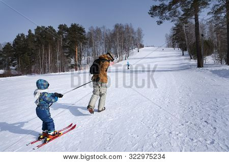 Professional Ski Instructor Is Teaching A Child To Ski. Family And Children Active Vacation. Sunny D