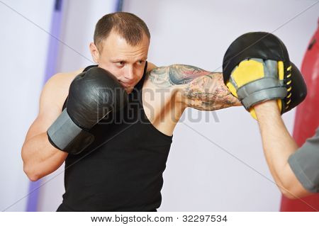 boxer man during boxing hiting mitts at training fitness gym poster