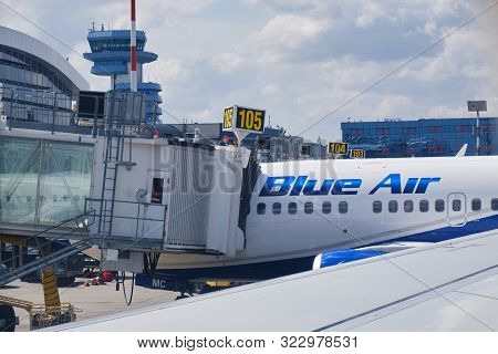 Otopeni, Romania - September 11, 2019: Blue Air Plane Connected To A Passenger Boarding Bridge At He