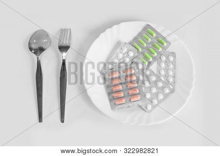 Different Pills On A Plate With Cutlery. The Concept Of Prescription Drugs For Weight Loss. Means Fo