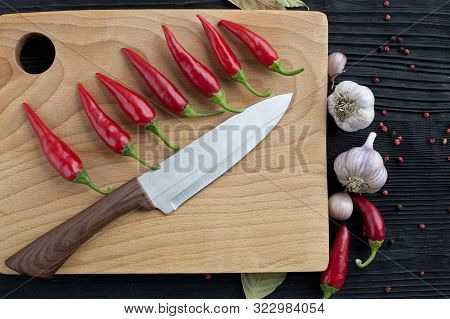 Big Chef  Knife Garlic Wooden Board Chili On A Dark Background