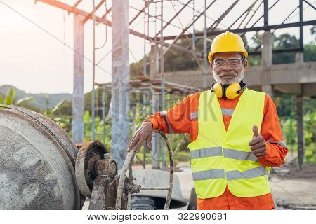 Construction Workers Wearing Safety Clothing Worker On Building Site Mixing Cement At Construction S