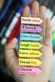 Positive words in hand. Todays goals list. Morning inspirational words - Smile often. Think positively. Give thanks. Laugh loudly. Love others. Dream big. Cherish every moment. With notes on colorful origami papers in open hand background. Motivational qu poster