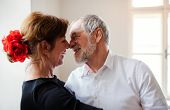 Affectionate senior couple attending dancing class in community center. poster