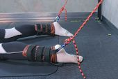 Instructor fasten ropes fixators sportsman legs prepare for myofascial stretching in trainer equipment in gym closeup. Stretch muscles, ligaments, tendons. Professional sport fitness training mashine. poster