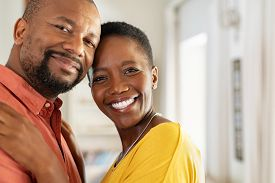 Portrait of romantic mature couple embracing and looking at camera. Smiling black man and woman together in new home. Closeup face of satisfied happy couple in their new apartment with copy space.