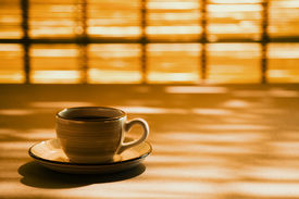 Coffee cup on patterned shadows background