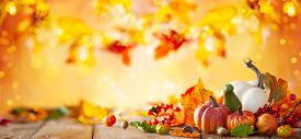 Autumn background from fallen leaves and pumpkins on wooden vintage table. Autumn concept with red-yellow leaves background. Thanksgiving pumpkins.
