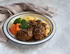 Close Up Of Plate With Salisbury Steak, Mushrooms, Mashed Potato, Broccoli, Carrots And Gravy On Gra