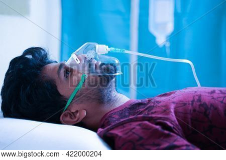 Side View On Young Man Breathing On Ventilator Oxygen Mask At Hospital Due Coronavirus Covid-19 Dysp
