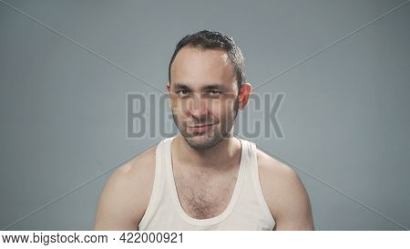 Photo Of Young Bristly Grinning Man On Grey