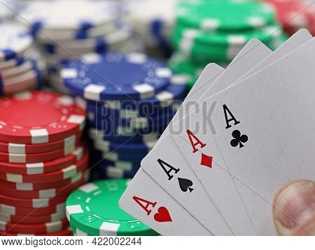 Four Aces Card Combination Holden In Front Of Stacked Casino Chips