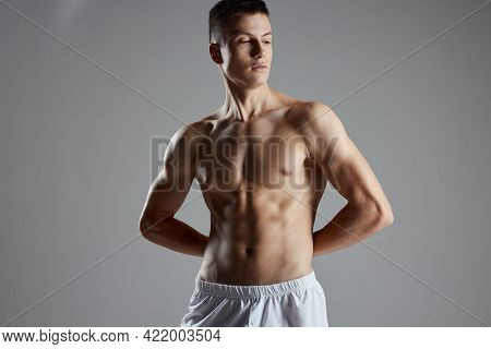 Athlete With Pumped Up Abs Holding Hands Behind His Back On Gray Background