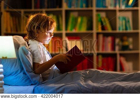Child Reading Book In Bed. Kids Read At Night.