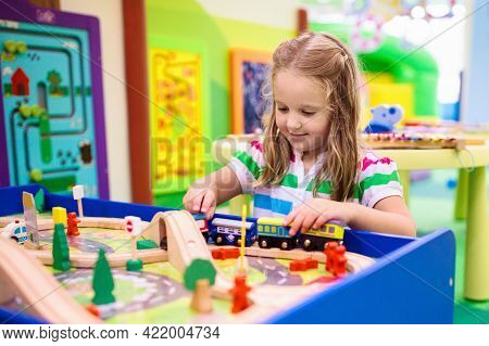 Kids Play Toy Railroad. Little Blond Curly Boy With Wooden Trains In Indoor Playground Or Amusement
